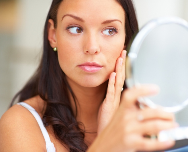 Closeup portrait of young lady holding a mirror